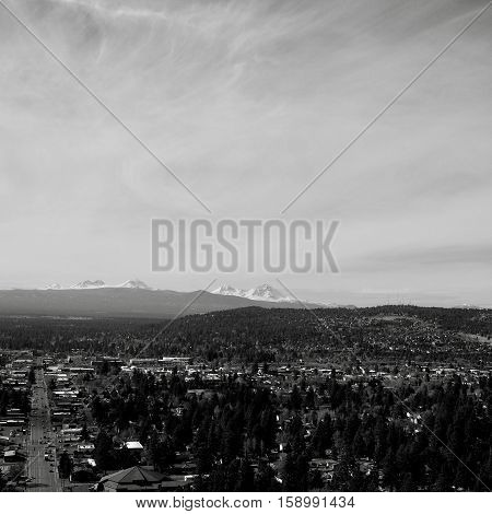 The city of Bend in Central Oregon on a sunny day with the Three Sisters in the Cascade Mountain Range in the background. Greenwood Avenue viewed from Pilot Butte.