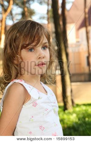 Portrait of little cute girl with curly blonde hair in white clothes inside green forest in front of house