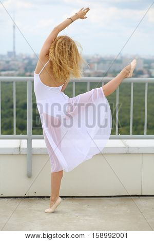 Beautiful girl in white dancing near railing on the roof of a multistory building, view from the back