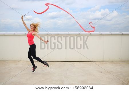 Beautiful blonde jumping with red curly ribbon on the roof of a multistory building against the cloudy sky