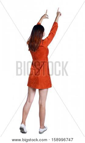 Back view of  pointing woman. beautiful girl. Rear view people collection.  backside view of person.  Isolated over white background. The girl in a red dress shows two hands up.