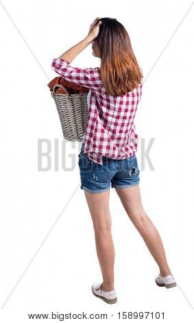 Back view of woman with  basket of dirty laundry. girl is engaged in washing. Rear view people collection.  backside view of person. The girl in a checkered shirt carries tired linen to the laundry.