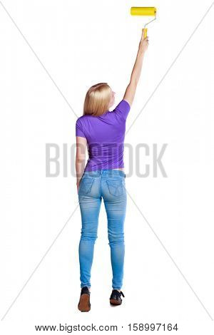 Back view of a girl who paints the paint roller. rear view people collection. backside view of person. Isolated over white background. Long-haired blonde in the purple shirt top paint roller.