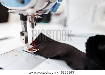 Sewing machine stitching dark fabric close-up. Detail photo of shuttle of needle working process. Garment industry, seamstress workplace, tailor workshop concept
