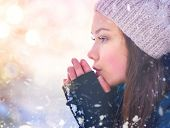 Winter girl blowing on her hands, cold weather. Snow. Frost, Freeze, Teenage Model Girl walking in w poster