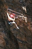 image of sling bag  - A rock climber works his way up a rock face protected by a rope clipped into bolts. He is wearing a helmet and quickdraws dangle from his harness. The route is in the desert southwest United States. Mt Lemmon Arizona.