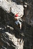 foto of sling bag  - A rock climber works his way up a rock face protected by a rope clipped into bolts. He is wearing a helmet and quickdraws dangle from his harness. The route is in the desert southwest United States. Mt Lemmon Arizona.