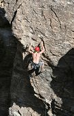 stock photo of sling bag  - A rock climber works his way up a rock face protected by a rope clipped into bolts - JPG