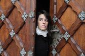 pic of open door  - Woman coming out of an ancient door - JPG