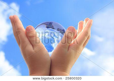 Globus in untergeordneten Händen gegen blauen Himmel.