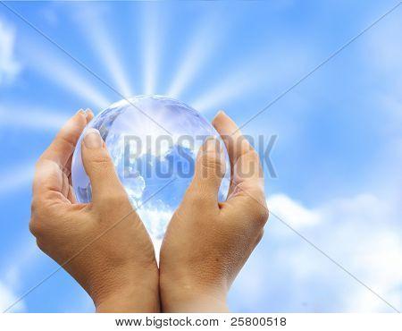 Globo en mano humana contra sol y azul cielo. Concepto de protección del medio ambiente.