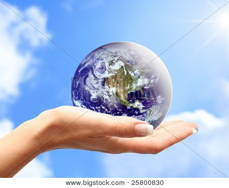 Globus in menschliche Hand gegen blauen Himmel. Umweltschutz-Konzept.