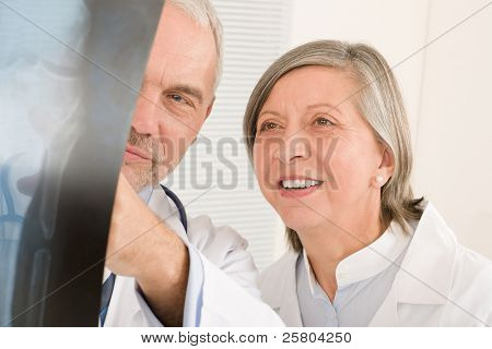 Medical doctor team senior man with female colleague look x-ray