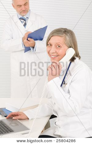 Medical senior doctor female calling with professional male colleague office