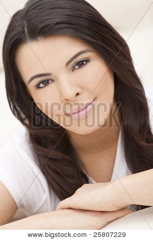 Studio portrait of a beautiful young Latina Hispanic woman resting on her hands