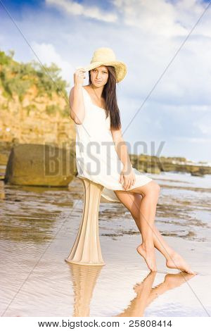 Elegant Woman With Hat Sitting At The Beach