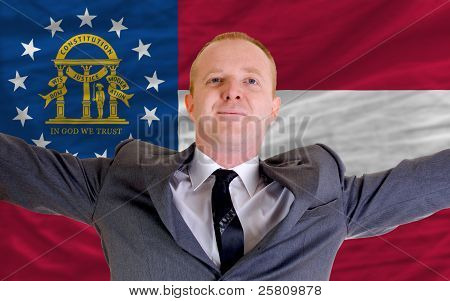 Happy Businessman Because Of Profitable Investment In Georgia Standing Near Flag