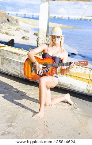 Smiling Girl Strumming Guitar At Tropical Beach