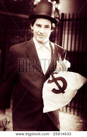 Male Banker Holding Dollar Sign Money Bags