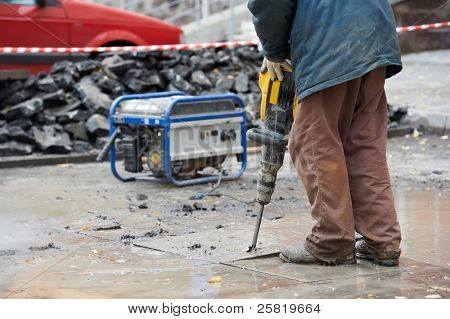 Builder worker with pneumatic hammer drill equipment breaking asphalt at construction site