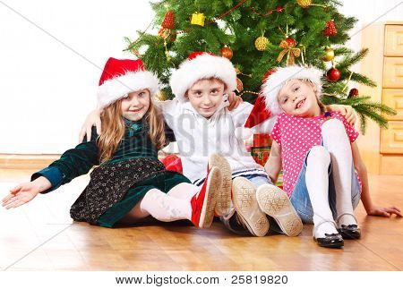 Group of cute kids in Santa hats, embracing