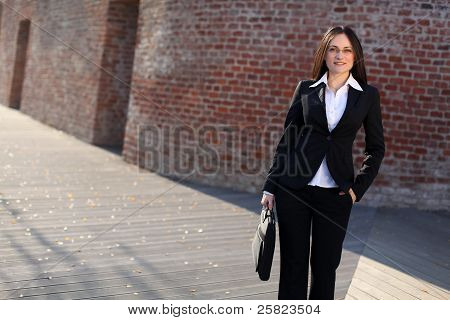 A Busineswoman Is Standing In Front Of A Brick Wall