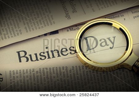 Loupe Lies On The Newspaper With Title Business Day.selective Lighting On An Inscription.