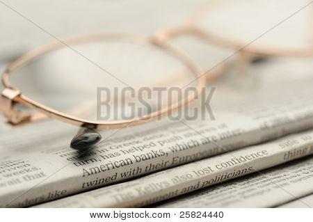 Eyeglasses Lie On A Pile Of Newspapers