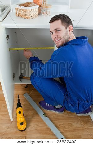 Portrait of a smiling repair man measuring something in a kitchen