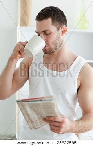 Portrait of a young man drinking tea while reading the news in his kitchen