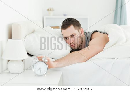 Exhausted man switching off his alarm clock in his bedroom