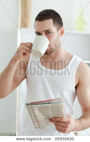Portrait of a handsome man drinking tea while reading the news in his kitchen