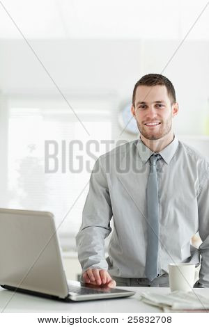 Portrait of a businessman using a laptop while drinking tea in his kitchen