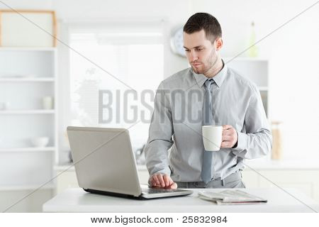 Businessman using a laptop while drinking coffee in his kitchen