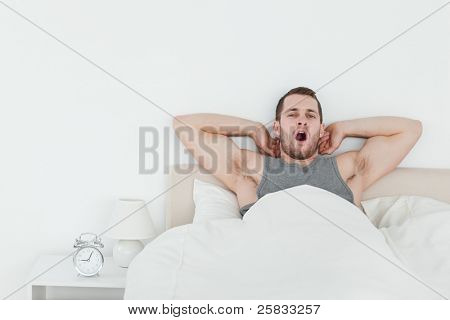 Man yawning while waking up in his bedroom