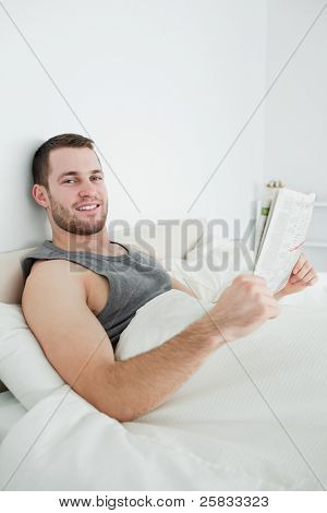 Portrait of a smiling man reading a newspaper in his bedroom