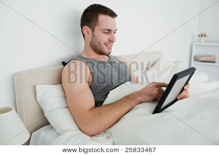 Happy man using a tablet computer in his bedroom