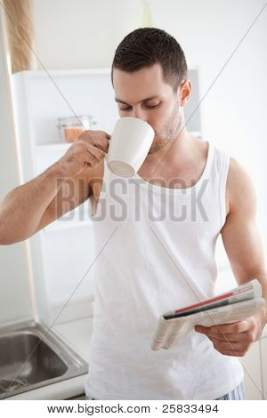 Portrait of a smiling man drinking tea while reading the news in his kitchen