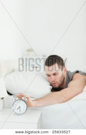 Portrait of a tired man being awakened by an alarm clock in his bedroom