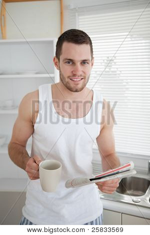 Portrait of a man drinking coffee while reading the news in his kitchen