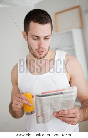 Portrait of a young man reading the news while drinking orange juice in his kitchen