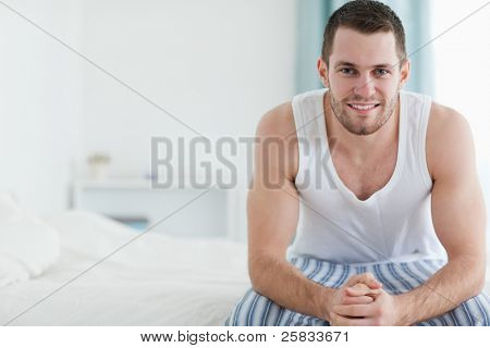 Happy man sitting on his bed while looking at the camera