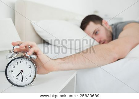 Young man being awakened by an alarm clock in his bedroom