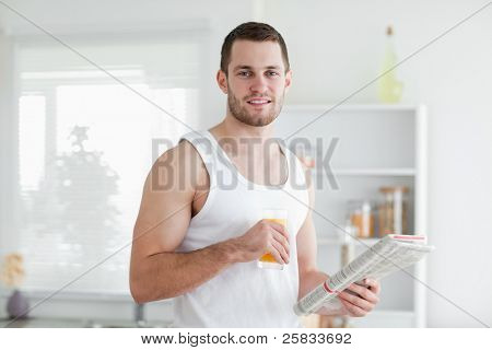 Smiling man drinking orange juice while reading the news in his kitchen