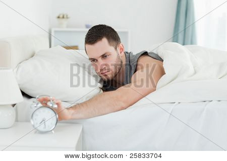 Tired man being awakened by an alarm clock in his bedroom