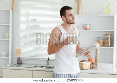 Good looking man drinking coffee while reading the news in his kitchen