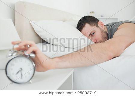 Homem atraente, sendo acordado por um despertador em seu quarto