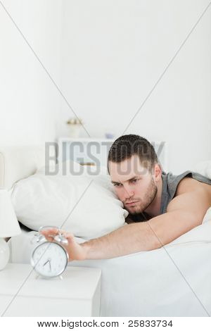 Portrait of a unhappy man being awakened by an alarm clock in his bedroom