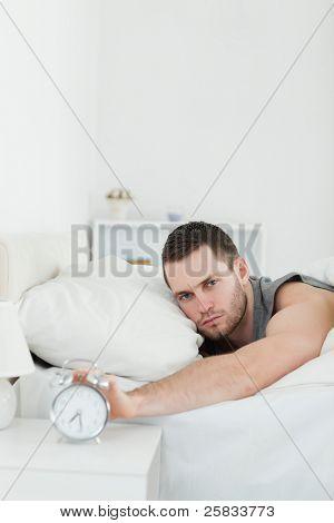 Retrato de um homem bonito, sendo acordado por um despertador em seu quarto