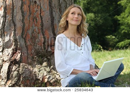 Young woman sat by tree with laptop